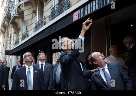 US President Barack Obama looks up and waves as he and French President Franois Hollande depart a restaurant after - Stock Photo