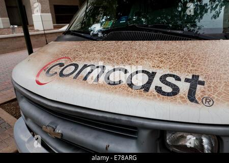 Dirty, worn-out, fading Comcast logo on service van - Arlington, Virginia USA - Stock Photo
