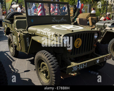 A vintage American jeep from World War II flying the American flag in a commemoration of the liberation of France. - Stock Photo