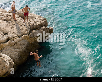 Boys diving off cliffs into the blue sea in Nice, France - Stock Photo