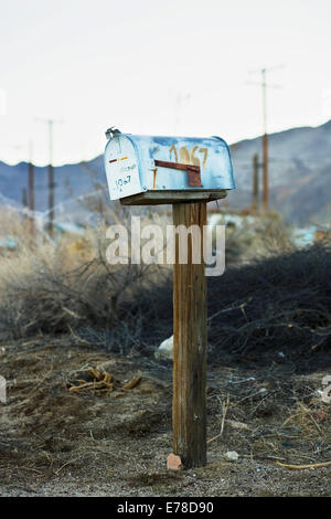 an old blue American mailbox on a wooden post stands rusting, abandoned and alone in front of a rocky skyline on - Stock Photo