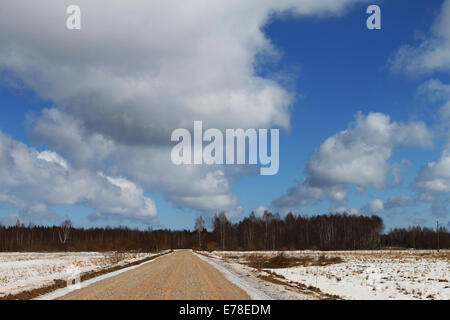 Country dirt road with snow on sides under high cloudy sky - Stock Photo