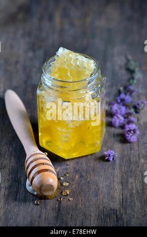 honeycomb and honey in glass jars , stiil life - Stock Photo