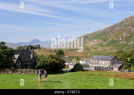 View to the rural village with two walkers walking down the hillside In Snowdonia National Park. Capel Curig, Conwy, - Stock Photo