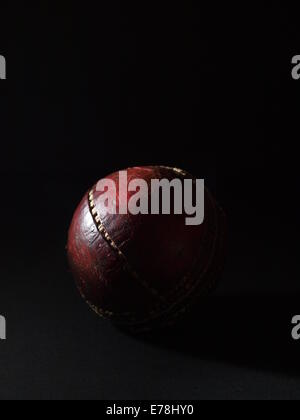Old, red leather cricket ball with stitching coming apart on black background - Stock Photo