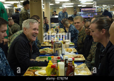 U.S. Secretary of the Navy Ray Mabus, left, has dinner with U.S. Sailors and Marines aboard the amphibious assault - Stock Photo