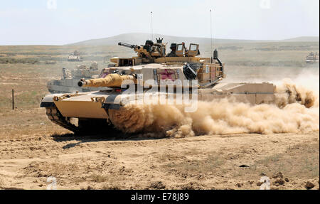 A U.S. Army M1A2 Abrams main battle tank assigned to the Minnesota National Guard races through a breach in a barbed - Stock Photo