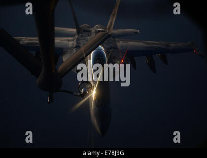 A U.S. Air Force KC-135 Stratotanker aircraft refuels a Navy F/A-18F Super Hornet aircraft assigned to Strike Fighter - Stock Photo
