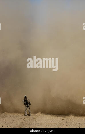 U.S. Marine Corps Cpl. Ryan Hamman, a vehicle commander with Bravo Company, 1st Battalion, 2nd Marine Regiment, turns his back against dust created by an Army UH-60 Black Hawk helicopter during a security patrol in Helmand province, Afghanistan, Aug. 24,