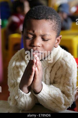 Christian Catholic child boy praying inside of a church ...
