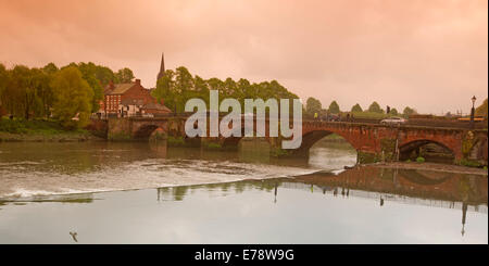 Iconic arched road bridge crossing the River Dee in Chester with segment reflected in calm water under pink evening - Stock Photo