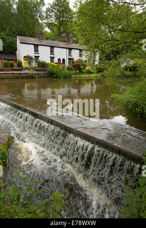 Water running over weir from lake with white painted cottages and colourful gardens on the bank at English village - Stock Photo