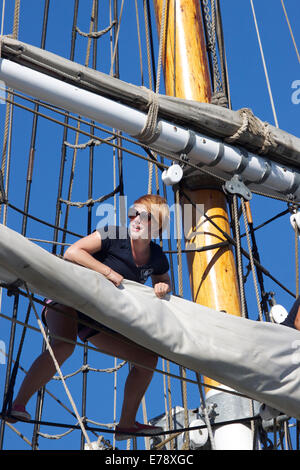 Crew member of the brigantine Exy Johnson tend to the rigging & sails at the Toshiba Tall Ships Festival Dana Point - Stock Photo