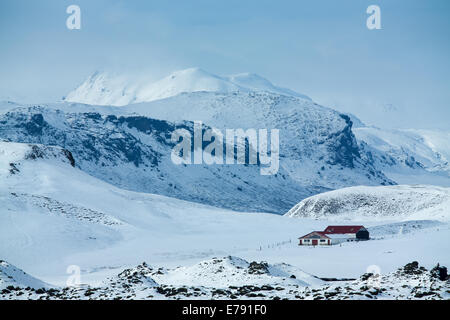 an isolated farmhouse in the snow with the mass of Katla beyond, southern Iceland - Stock Photo