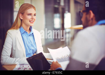Smiling businesswoman looking at her colleague while speaking to him at meeting - Stock Photo