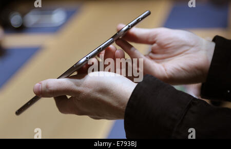 Cupertino, California, USA. 9th September, 2014. A hand holds two versions of Apple's new iPhone 6 during the product - Stock Photo