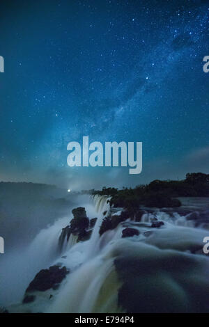 the Milky Way over Iguazu Falls at night, Argentina - Stock Photo