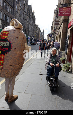Lady on mobility scooter passing man dressed as a Haggis. Canongate The Royal mile.Edinburgh Scotland. - Stock Photo