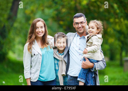 Happy family members looking at camera in natural environment - Stock Photo