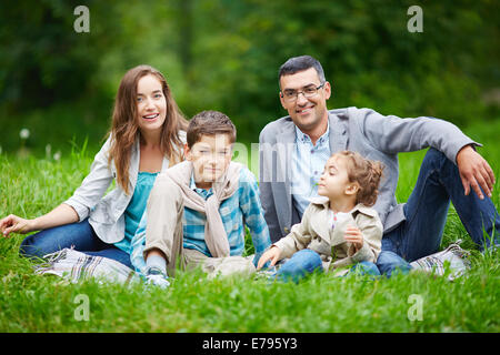 Happy family members looking at camera while sitting in green grass outdoors - Stock Photo
