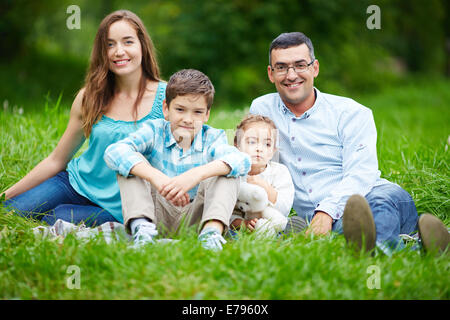 Happy family members looking at camera while sitting on the lawn - Stock Photo
