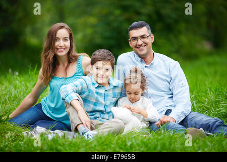 Happy family members relaxing on the lawn in summer - Stock Photo