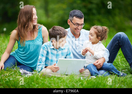Happy couple spending time in the park with their children - Stock Photo