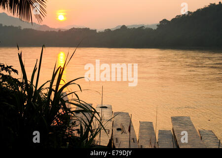 The sun begins to set over the dense jungle as another day comes to an end in Luang Prabang. - Stock Photo