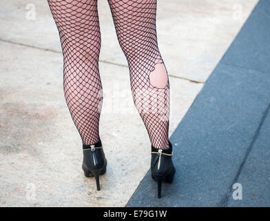 A fashionista pose with torn fish-net stockings outside of the Spring 2015 Fashion Week shows in Lincoln Center - Stock Photo