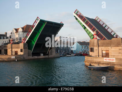 Town bridge raised to allow a yacht to pass into the marina in Weymouth harbour, Dorset, England - Stock Photo