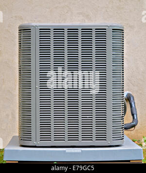 An air conditioner compressor on the side of a house. - Stock Photo