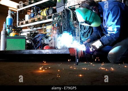 Welder in work with welding in the workshop - Stock Photo