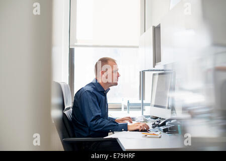 A man working in an office at a desk using a computer mouse. Focusing on a task. - Stock Photo