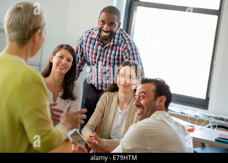 Five people in an office, two men and three women talking. - Stock Photo