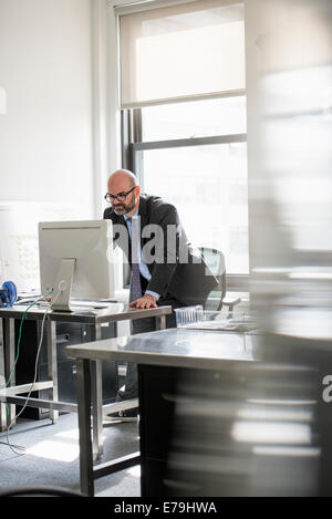 Office life. A man working alone in an office. - Stock Photo