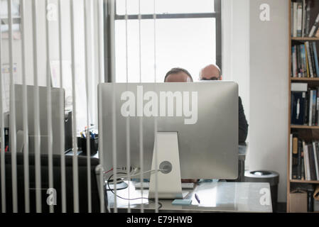 Office life. Two people seated at a desk behind a computer terminal. - Stock Photo