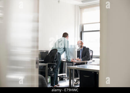 Office life. Two people talking to each other over a desk. - Stock Photo