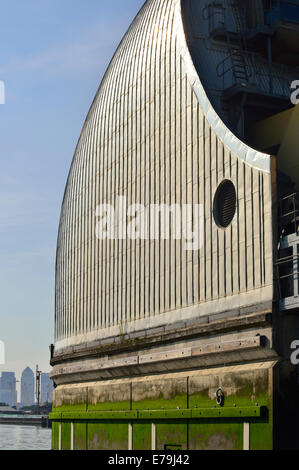 One of the Thames Barriers across  on the River Thames near Woolwich with Canary Wharf in the distance - Stock Photo