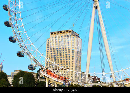 Detail of the London Eye giant Ferris wheel South Bank of the River Thames in London with the Shell building behind - Stock Photo
