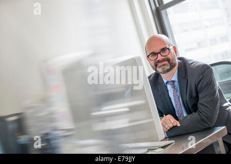 Office life. A man in a suit and tie sitting at his desk looking around his computer. - Stock Photo
