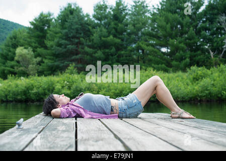 A woman lying on the jetty by a lake in summer - Stock Photo
