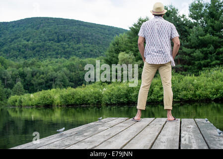 A man standing on a wooden pier overlooking a calm lake. - Stock Photo
