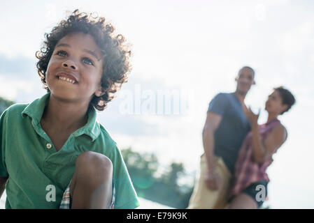 A family, parents and son by a lake in summer. - Stock Photo