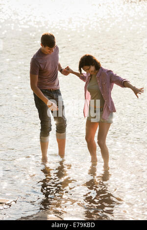 A couple holding hands, paddling in shallow water at the lake. - Stock Photo