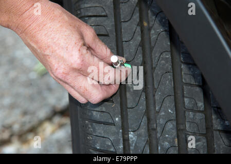 Woman using tyre depth gauge to check the depth of the tread - Stock Photo