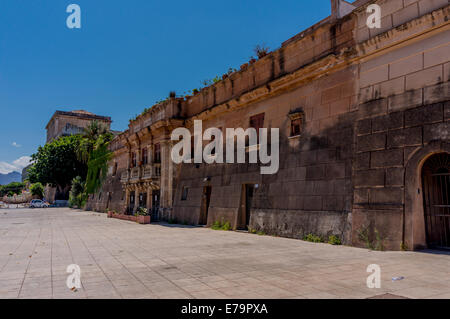 Tarnished old buildings by the seafront in Palermo, Sicily, built in a wall-like structure - Stock Photo