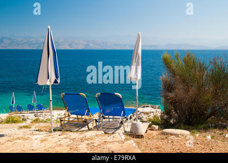 Sunbeds and umbrellas (parasols) on a rocky beach in Corfu Island, Ionian Sea, Greece - Stock Photo