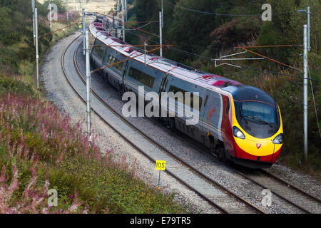 Power lines, and gantries for electric trains _ British Railways carriages descending Virgin Voyager Train at Shap, - Stock Photo