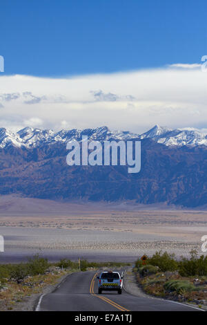 State Route 190 climbing up from Death Valley over Panamint Range, with snowy Grapevine Mountains in background, - Stock Photo
