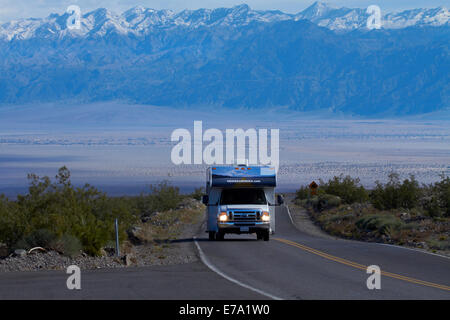 RV on State Route 190 climbing up from Death Valley over Panamint Range, with snowy Grapevine Mountains in background, - Stock Photo